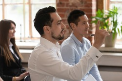 Multi ethnic people take part in seminar, side view focus on middle eastern man raising hand to ask question at corporate training for express personal opinion on issue, educational lecture concept