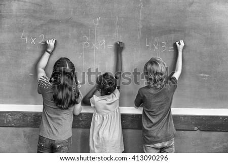 Multi ethnic primary school classroom writing with chalk at blackboard.