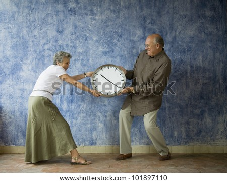 Multi-ethnic senior couple having tug of war with clock