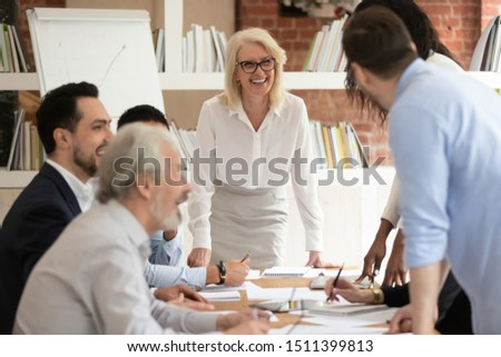 Multi-ethnic team members takes part in briefing lead by aged businesswoman company boss, businesspeople feels satisfied succeed agreement acceptable to both parties, mentoring or negotiations concept