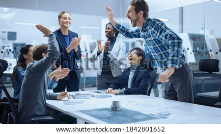 Multi Ethnic Team of Industrial Engineers Standing at the Conference Table Successfully Solve Project Problems, They're Happy and Celebrate with High Five and Cheers. Modern Factory.