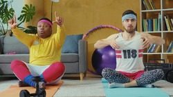 Multi-ethnic team of retro styled guys practicing yoga together at home. Funny stupid-looking unfit jerks doing meditation exercises on mats in living room.