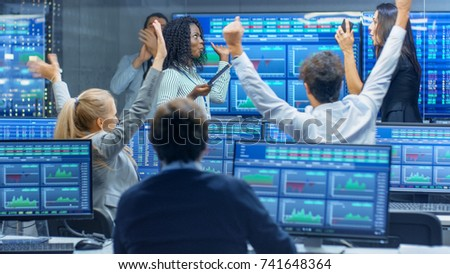 Multi-Ethnic Team of Traders Have Successful Day at the Stock Exchange Office. Dealers and Brokers Buy and Sell Stocks on the Market, they Celebrate Profitable Transaction.