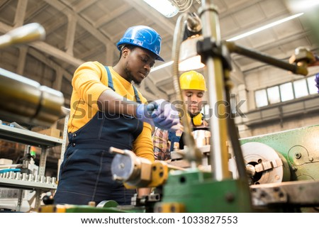 Multi-ethnic team of workers wearing overalls and protective helmets using lathe in order to machine workpiece, interior of spacious production department on background