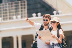 Multi-ethnic traveler couple using local map together on sunny day, man pointing forward to copy space. Honeymoon trip, backpacker tourist, Asia city tourism, or summer holiday vacation travel concept