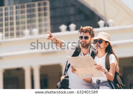 Photo of  Multi-ethnic traveler couple using local map together on sunny day, man pointing forward to copy space. Honeymoon trip, backpacker tourist, Asia city tourism, or summer holiday vacation travel concept