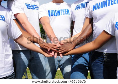 multi-ethnic volunteer group hands together showing unity - stock photo