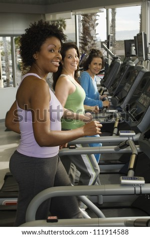 Multi ethnic women exercising on treadmill