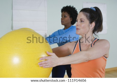 Multi ethnic women using exercise balls in fitness class