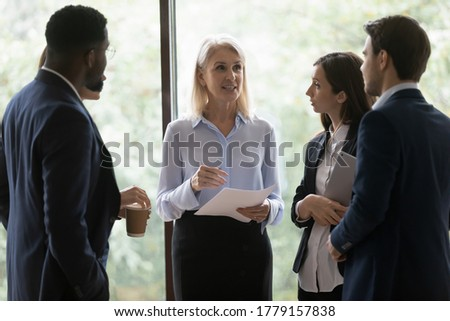 Multi ethnic young office employees young professionals staff members surround middle-aged boss female leader ask questions listen guidance feels focused and interested. Mentoring, leadership concept