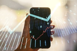 Multi exposure of abstract financial graph with upward arrow and hand with mobile phone on background, financial and trading concept
