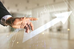 Multi exposure of man hand working with abstract financial diagram and upward arrow on blurred office background, rise and breakthrough concept