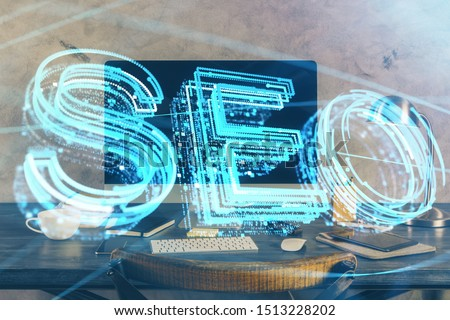 Multi exposure of table with computer and seo drawing hologram. Search optimization concept.