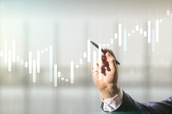 Multi exposure of trader hand with pen working with virtual abstract financial graph interface on blurred office background, financial and trading concept