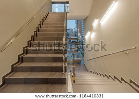 Multi-flight stairway with stainless handrails and panoramic windows. FIRE ESCAPE. EMERGENCY EXIT. FIRE EXIT