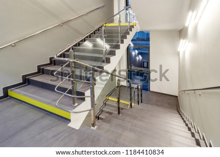 Multi-flight stairway with stainless handrails and panoramic windows. FIRE ESCAPE. EMERGENCY EXIT. FIRE EXIT.