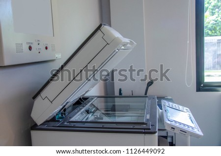 Multi function photocopier is a machine in office that makes paper copies of documents and other visual images ,close-up shot on working multi-function device, photocopier,office life, fax, copy #1126449092