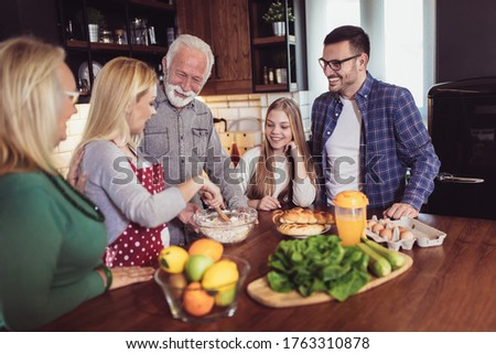 Multi Generation Family Cooking Meal At Home stock photo