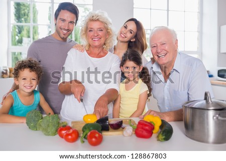 Multi-generation family cutting vegetables together in the kitchen