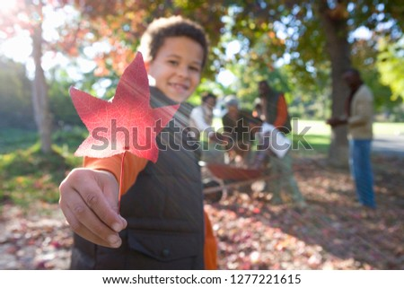 Multi-generation family doing yard work clearing autumn leaves
