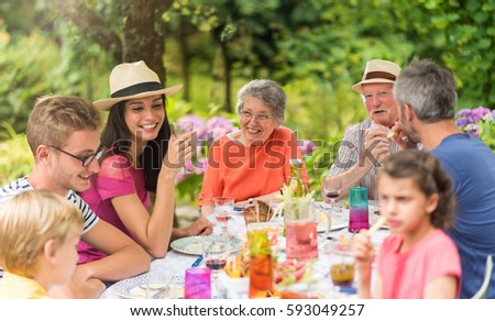Multi generation family gathered to lunch in the garden in summer, they having fun sitting around a picnic table stock photo