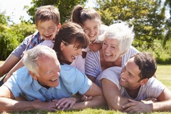 Multi Generation Family Piled Up In Garden Together