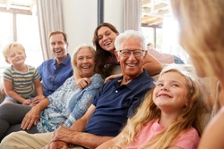 Multi-Generation Family Sitting On Sofa At Home Relaxing And Chatting