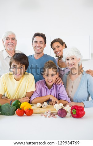 Multi generation family smiling in kitchen beside chopping board
