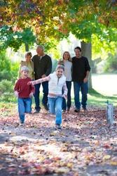 Multi-generation family walking through autumn park