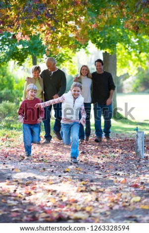 Multi-generation family walking through autumn park