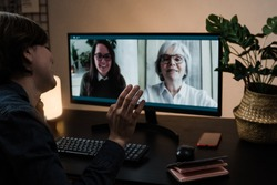 Multi generational business women having video call with her colleagues using computer app - Soft focus on right hand