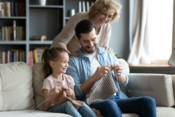 Multi generational family enjoy common hobby, aged woman grandmother looking with love her adult son his little daughter knitting seated on couch in living room, pastime, spend time together concept