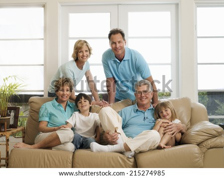 Multi-generational family relaxing on sofa at home, smiling, portrait