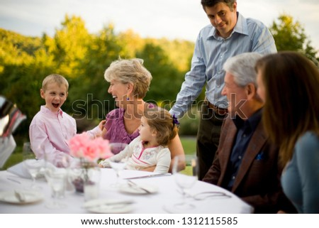 Multi-generational family sitting at an outside table of a restaurant watching a young boy be entertaining.