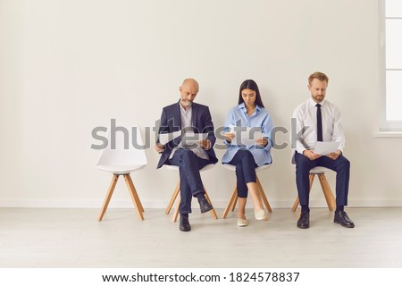 Multi-generational workforce. Three diverse applicants sitting in queue in office waiting for interview. Multiracial job seekers line up in corridor of business company. Copyspace Stock photo ©