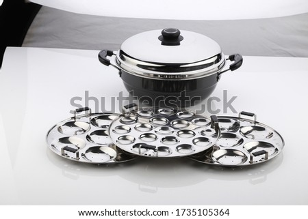 Multi Kadai Induction & Standard Idli Maker.Idli on idli maker- Healthy and traditional breakfast dish in South India,square composition.stainless steel idli maker with plain plate. maker isolated