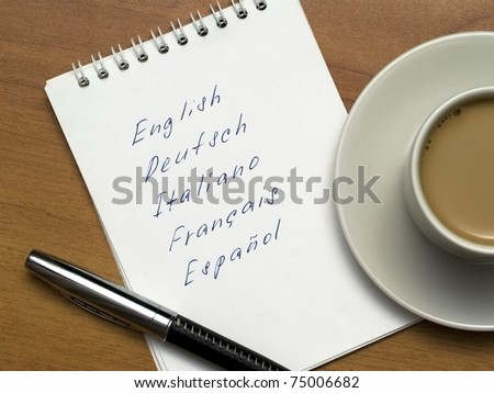 multi-languages list in a notebook with a pen and a cup of coffee on a wooden background