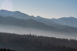Multi layered mountainscape view. Tatra Mountains on a sunny December day. The fog is in the valleys between the ridges. Selective focus on the forest, blurred background.