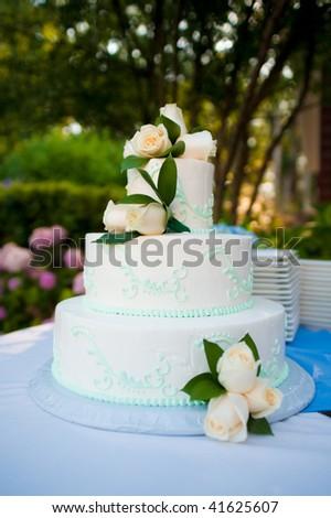 Multi-layered white wedding cake with roses