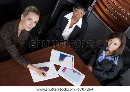 Multi-racial business team working within an office with a sales graphs