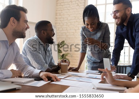 Multi racial employees laughing during briefing in boardroom, colleagues do paperwork analyze statistics financial report in charts and graphs take break having fun telling jokes enjoy pause concept