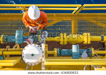 Multi skill operation technician calibrating oil field instrument, Coriolis flow meter and actuated control valve on offshore oil and gas platform.