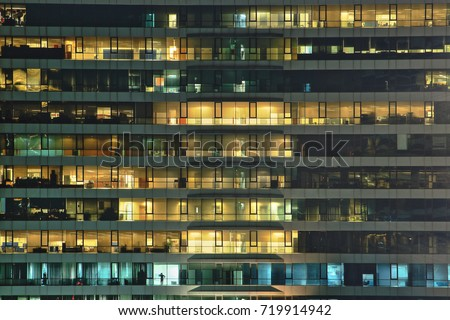 multi-storey office building at night with worker working overtime. late night at office. lighting and working people within. Late night overtime in a modern office building