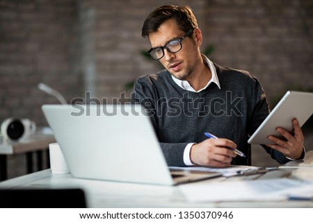 Multi-tasking businessman working in the office. He is using touchpad while reading an e-mail on laptop and taking notes on the paper.