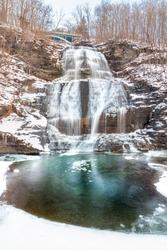 Multi tiered waterfall cascading down rocks in a snowy winter wonderland scene. She-Qua-Ga Falls - Montour Falls New York.