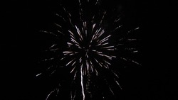 Multico lored fireworks in night sky. Shining fireworks with bokeh lights in night sky. Glowing fireworks show. New year's eve fireworks celebration. Beautiful colored night explosions in black sky