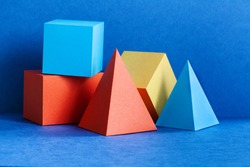 Multicolor geometrical figures still life composition. Three-dimensional prism pyramid rectangular cube objects on blue background. Platonic solids figures, simplicity concept