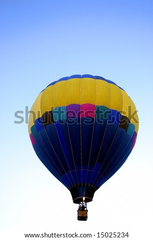 Multicolor hot air balloon against blue graduated sky with room for text