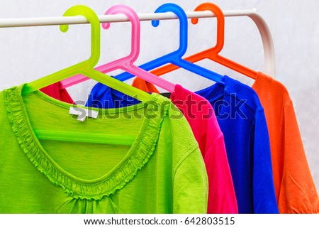 Multicolor Ladies blouses on Multicolor plastic clothes hangers, summer fashion background #642803515