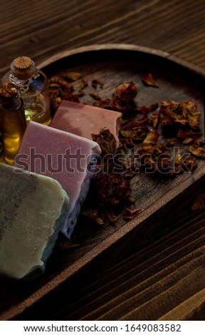 Multicolor natural bar soaps with essential oil and dry roses on wooden rustic background.
